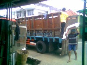 Para pekerja sedang menurunkan beras di toko beras Makmur Pangan.
